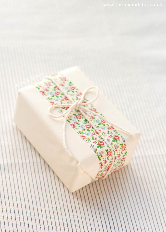 Christmas Gift wrap - vintage style Christmas gift wrap with white paper, red and pink floral washi tape and a simple yarn bow. A beautifully elegant idea for wrapping a small Christmas gift #giftwrap #christmas #christmasgiftwrap #simpleChristmas #vintagechristmas #washitape #yarn